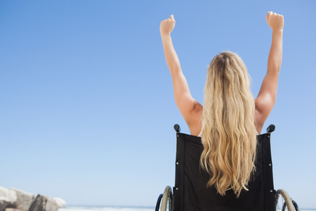 Wheelchair bound blonde sitting on the beach with arms up on a sunny day photo