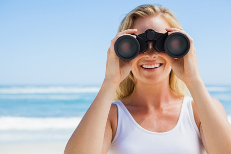 Blonde looking through binoculars on the beach on a sunny day photo