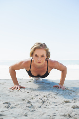 plank position: Fit blonde in plank position on the beach on a sunny day Stock Photo