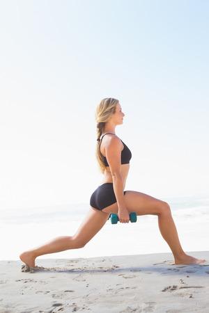 lunges: Montar rubia haciendo estocadas ponderados en la playa en un d�a soleado