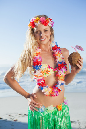 Gorgeous blonde in garland holding coconut drink on the beach on a sunny day photo