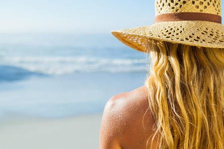 wavy hair: Gorgeous blonde in sunhat on the beach on a sunny day