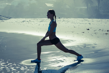 lunges: Fit woman doing lunges on the beach in the evening