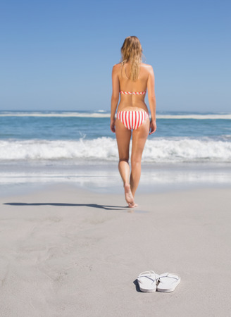 Fit woman in bikini walking towards the sea on a sunny day photo