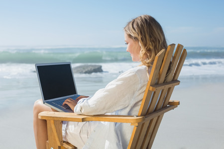 Gorgeous blonde sitting on deck chair using laptop on beach on a sunny day photo