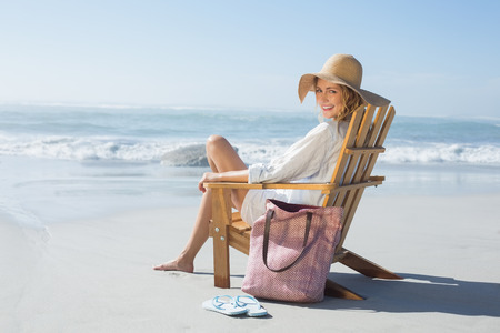 Smiling blonde sitting on wooden deck chair by the sea on a sunny day photo