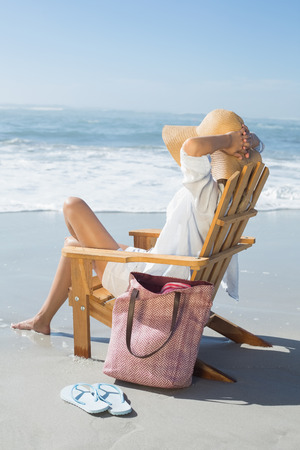 Woman sitting on wooden deck chair by the sea on a sunny day photo