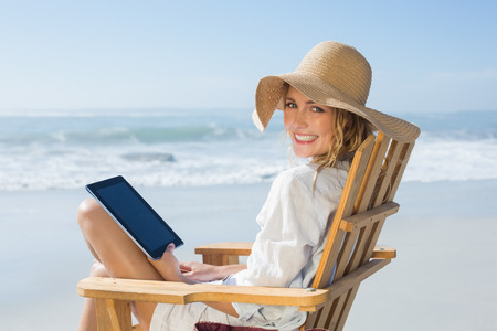 Smiling blonde sitting on wooden deck chair by the sea using tablet on a sunny day