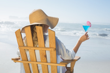 Woman relaxing in deck chair by the sea holding cocktail on a sunny day photo