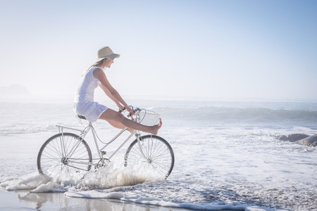 gorgeous: Gorgeous happy blonde on a bike ride at the beach on a sunny day Stock Photo