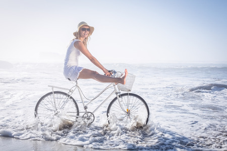 Gorgeous happy blonde on a bike ride at the beach on a sunny day photo