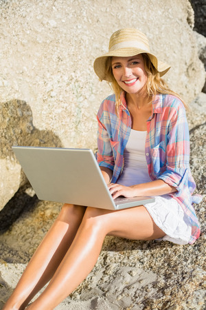Pretty blonde using laptop at the beach on a sunny day photo