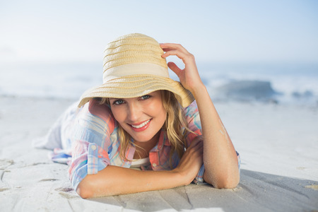 Pretty blonde smiling at camera at the beach lying on the sand on a sunny day photo