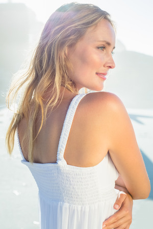 maxi dress: Pretty blonde standing at the beach in white sundress on a sunny day