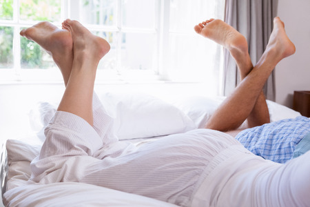 Couples legs lying on bed at home in the bedroom photo