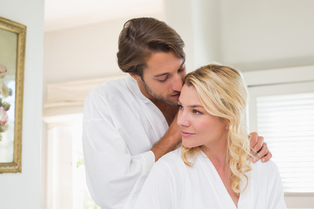 Cute couple in bathrobes spending time together at home in the living room photo