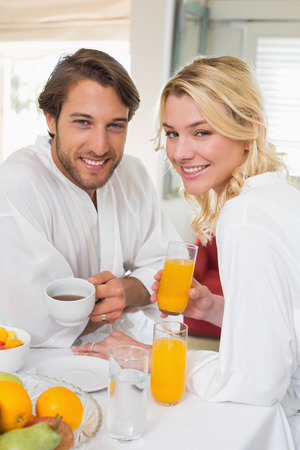 Cute couple in bathrobes having breakfast together smiling at camera at home in the living room photo