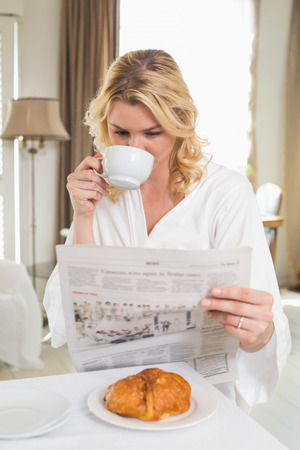 Pretty blonde in bathrobe drinking coffee and reading newspaper at home in the living room photo