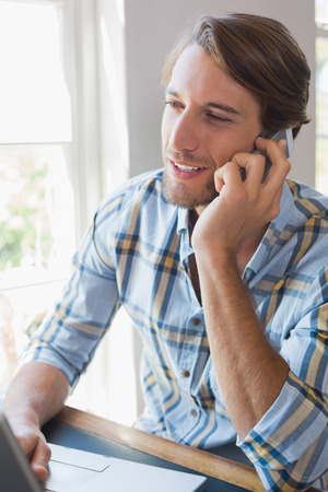 Smiling casual man using laptop and talking on smartphone at home in the living room photo