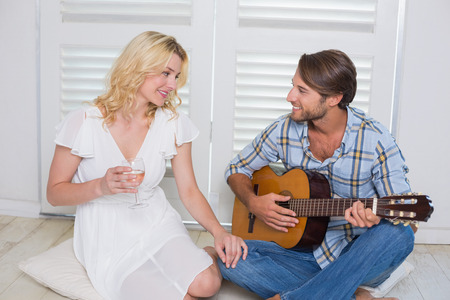Handsome man serenading his girlfriend with guitar at home in the living room photo