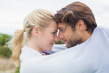 hair wrapped up: Cute affectionate couple standing outside wrapped in blanket on a chilly day