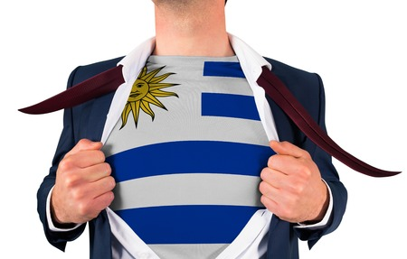 Businessman opening shirt to reveal uruguay flag on white background photo