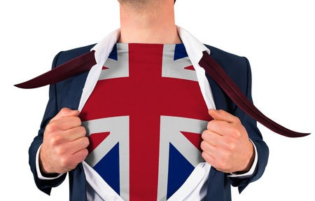 Businessman opening shirt to reveal union jack flag on white background photo