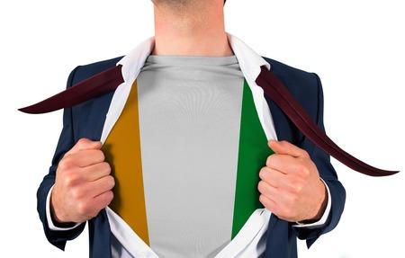 Businessman opening shirt to reveal ivory coast flag on white background photo
