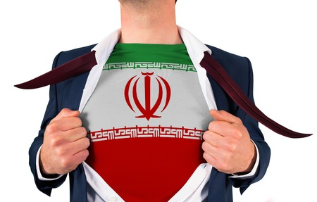 Businessman opening shirt to reveal iran flag on white background photo