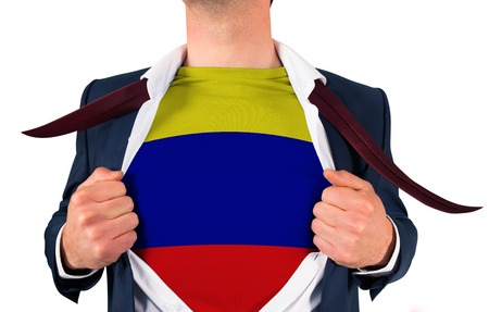 Businessman opening shirt to reveal colombia flag on white background