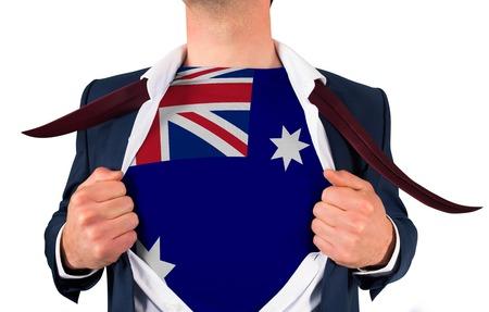 Businessman opening shirt to reveal australia flag on white background photo