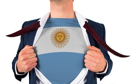 Businessman opening shirt to reveal argentina flag on white background photo