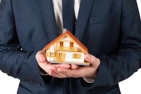 Businessman holding miniature house model on white background photo