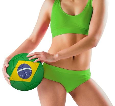 Fit girl in green bikini holding brasil ball on white background photo