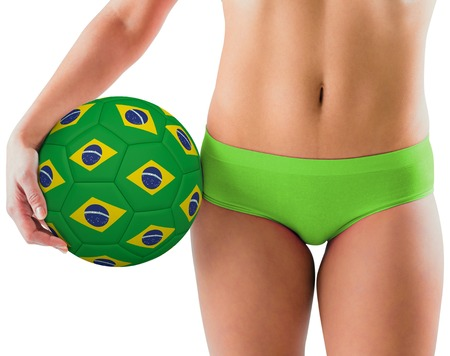 Fit girl in green bikini holding brazil football on white background photo