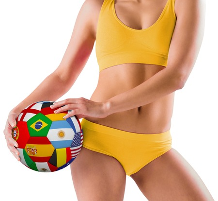 Fit girl in yellow bikini holding flag football on white background photo