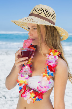 sipping: Pretty blonde in floral garland sipping cocktail on the beach on a sunny day Stock Photo