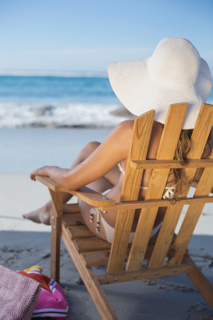 Woman in straw hat relaxing in deck chair on the beach on a sunny day photo