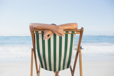 escapism: Woman relaxing in deck chair on the beach on a sunny day