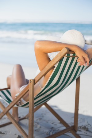 Slim woman relaxing in deck chair on the beach on a sunny day photo