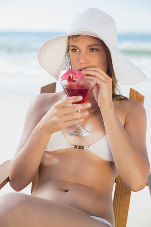 Pretty blonde relaxing in deck chair on the beach with cocktail on a sunny day photo