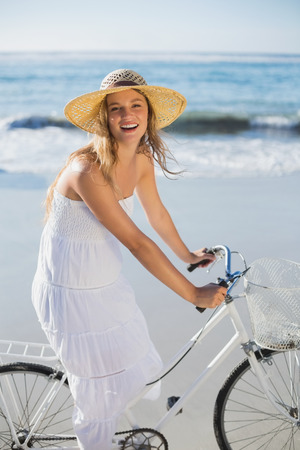 Beautiful blonde in white sundress on bike ride at the beach on a sunny day photo