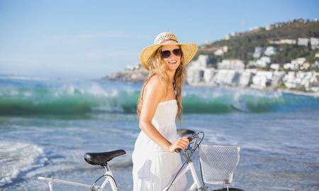 maxi dress: Beautiful smiling blonde in sundress with her bike at the beach on a sunny day