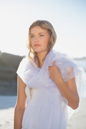 Beautiful blonde in white sundress and scarf on the beach on a sunny day photo