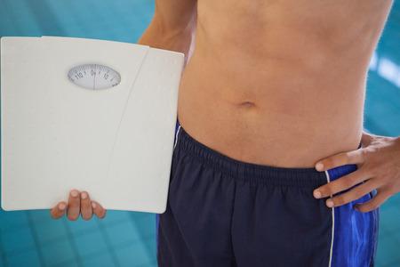 weighing scales: Fit uomo in costume da bagno in piedi dalla holding piscina bilancia al centro ricreativo