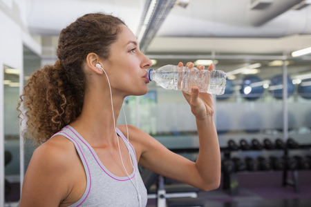 Fit woman drinking from water bottle at the gym Stock Photo