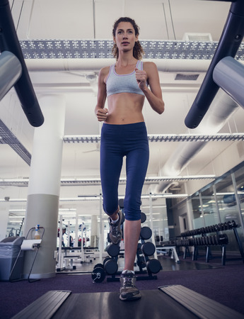 Fit woman running on the treadmill at the gym photo