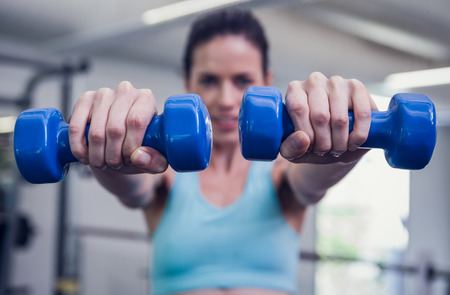 Smiling woman lifting blue dumbbells at the gym Stock Photo