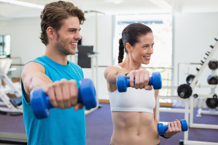 Fit couple exercising with blue dumbbells and smiling at the gym photo