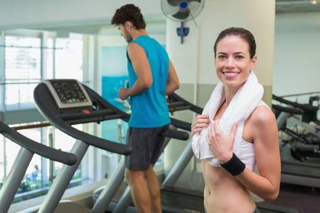 Fit brunette smiling at camera with towel around shoulders at the gym